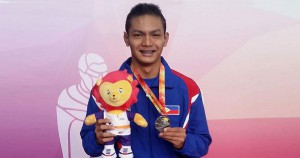 Sacho Ilustre holds his gold medal during the awarding ceremony of the ASEAN